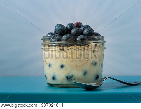 Overnight Oats In A Glass Jar Plate Decorated With Blueberries ,  Selective Focus, Blue Background A