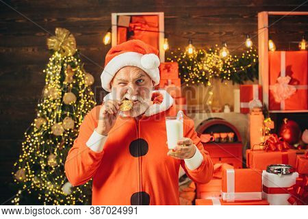 Portrait Of Bearded Funny Man In Santa Costume. Santa Claus Eating Cookies And Drinking Milk On Chri
