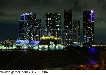 Cruise Ship In The Port Of Miami At Sunset With Multiple Luxury Yachts. Miami Night Downtown, City F