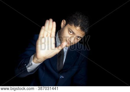 A Tired Man Saying No To Work Isolated On A Black Colored Background Wearing A Blue Colored Suit.