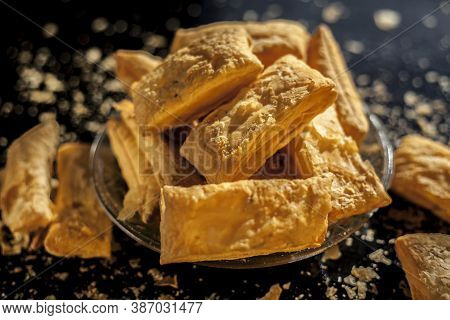 Classic Jeera Khari Or Puff Pastry In A Glass Plate On A Black Surface. Shot Of Freshly Baked Puff P
