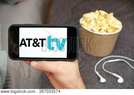 At And T Tv Logo On The Mobile Phone Screen With Popcorn Box And Apple Earpods On The Background. Le