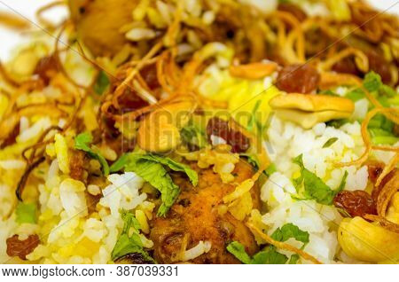 Closeup Of Chicken Biryani With Cashew, Fried Onions, Mint Leaves, Raisins Spread Over