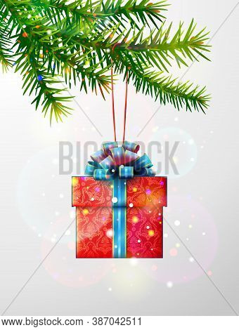 Christmas Tree Branch With Gift Box. Red Gift Decorated With Blue Ribbon And Bow Hanging On Pine Twi