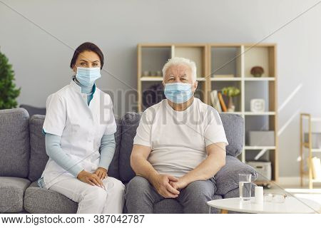 Portrait Of Therapeutist And Aged White-haired Man, Both Wearing Medical Face Masks, Sitting On Couc