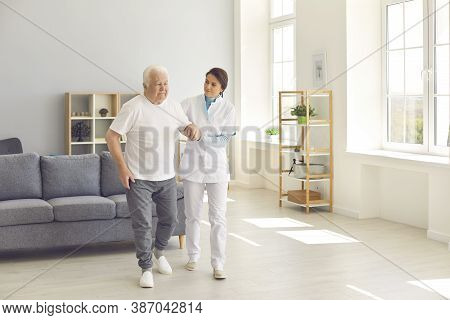 Healthcare Worker Helping Senior Man To Walk In Office Of Modern Hospital Or Geriatric Rehab Center