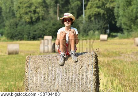 Girl Sitting On A Meadow After Harvest On A Stack Of Straw
