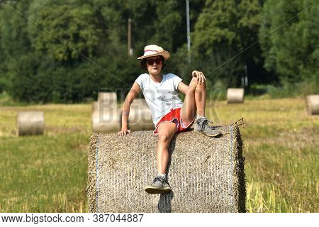 Girl In A Straw Hat Posing On A Straw Stack After Harvest