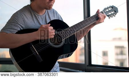 Young Man Or Musician Playing Guitar Against The Window At Home. Concept. Close Up Of A Man Holding