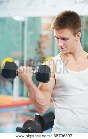 athlete man at biceps brachii muscles exercises with training dumbbells in fitness gym