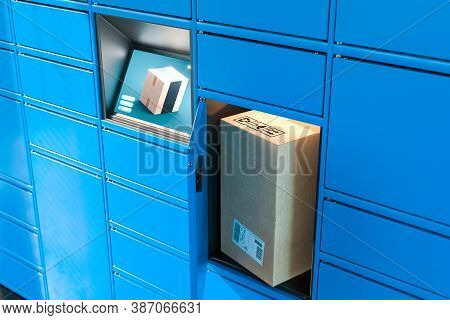 Close Up Of Light Blue Self-service Post Terminal Machine With Touchscreen Monitor And Open Locker W