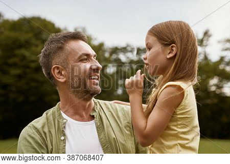 Daughter And Daddy. Cute Little Girl Spending Time With Father While Visiting Park On A Summer Day,