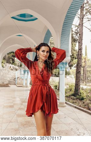 Beautiful Woman With Dark Hair In Elegant Red Dress And Accessories Posing In Beautiful Eastern Styl