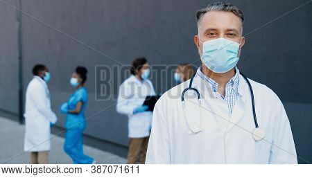 Portrait Of Caucasian Good-looking Man Doctor In Medical Mask And With Stethoscope Looking At Camera