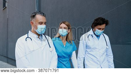 Caucasian Males And Female Doctors Colleagues In Medical Masks Walking Together And Talking Cheerful