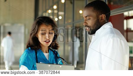 Mixed-races Male And Female Doctors Talking Joyfully In Clinic. Multi Ethnic Man And Woman, Medics H
