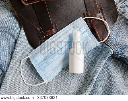 Bottle Of Hand Sanitizer, Antimicrobial Liquid Spray, Medical Protective Mask And Brown Bag On Blue