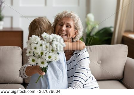 Excited Grandmother Embracing Little Granddaughter Grateful For Flowers On Holiday