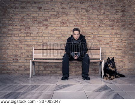 A Young Man, With His Black Dog Next To Him, Sitting On A Modern Bench In A Room With A Marble Floor