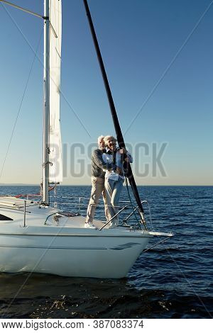 Full Length Of A Happy Senior Couple Hugging, Looking At The Horizon, Enjoying Amazing View While St