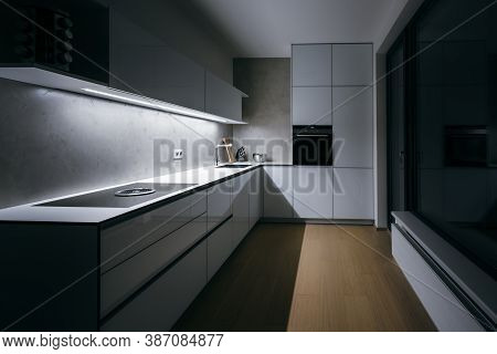 Modern Kitchen In Minimalist Design,in Night,with Light Strip,modern Appliances,wall-sockets And Pre