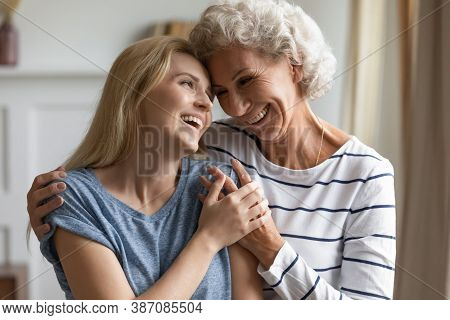 Tender Caring Silver God-mother Embracing Shoulders Of Beloved Grown God-daughter