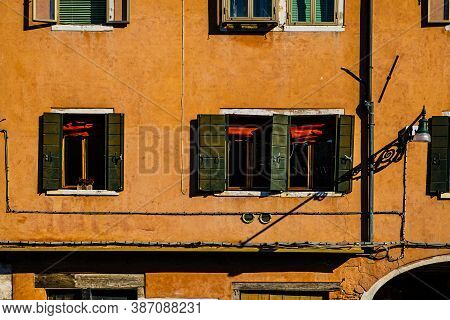 Italian Culture On Venetian Facades. Venice Is Rich And Poor, Well-groomed And Abandoned, Reflected