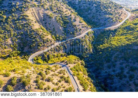 Mountainous Area. The Winding Road Runs Along A Steep Slope. Shooting From The Air.