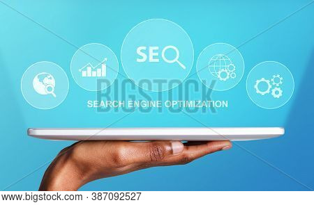 Search Engine Optimization. Black Male Hand Holding Digital Tablet With Seo Word And Seo-optimizatio