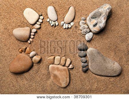 Trace-Fuß an ein Kiesel-Stein auf dem Meer-Sand-Hintergrund, Konzept glückliche Familie