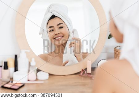 Young Smiling Asian Woman Wrapped In Towel Looking At Mirror In Bedroom, Drying Her Face After Morni