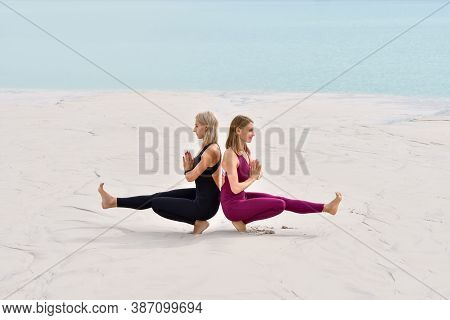 Two Beautiful Young Women Performing Yoga Exercises On The Beach