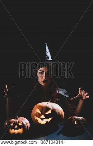 An Ominous Witch In A Hat Conjures Over A Jack-o-lantern. Traditional Halloween Characters. Mystical
