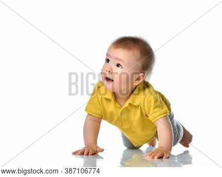 Curious Baby Boy Crawling Along On White Floor Studio Shot. Cute Lovely Interested Child With Inquis