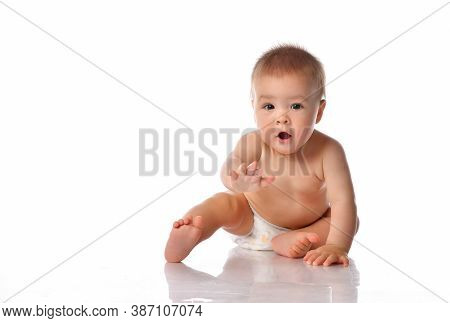 Little Baby In Nappy Sitting On Floor. Cute Toddler Child Stretching Out By Hand Trying To Reach For
