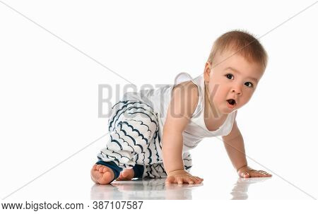 Cute Plump Baby Boy In Night-gown Crawling On Floor. Excited Toddler Child After Daydreaming Or Nigh
