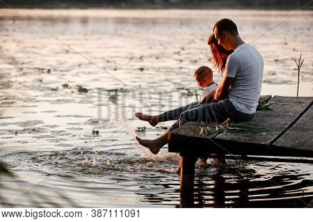 Young Parents And Their Little Son Sitting On The Wooden Pier Near The Lake, At Sunset On Summer Day