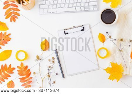 Flat Lay Blogger Or Freelancer Workspace With A Clipboard, Keyboard, Sweater And Colorful Autumn Lea