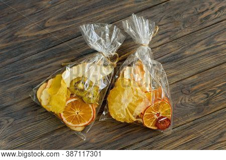 Set Of Dried Tropical Fruits Slices On Wooden Background. Mix Of Dried Pineapple, Kiwi, Orange, Melo