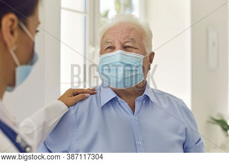 Happy Senior White-haired Patient In Medical Face Mask Trusting His Young Doctor
