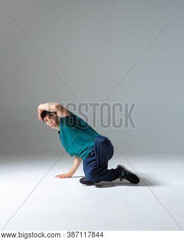 Guy Breakdancer Dancing Lower Break Dance In Studio Isolated On Gray Background