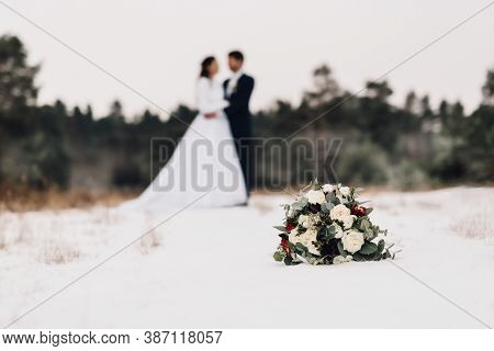 Wedding Bouquet Composed Of White Roses And Decorative Leaves. Bouquet Lies On Snowy Ground. In Back