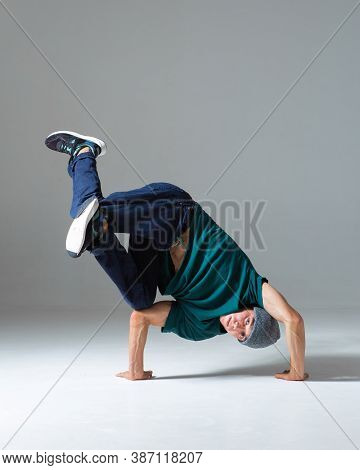 Stylish Young Guy Breakdancer In Hat Stands On Hands Dancing Hip Hop Isolated On Gray Background. Da
