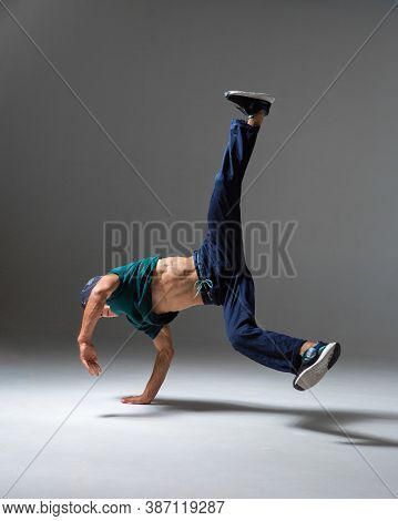Cool B-boy Dancing In Studio Isolated On Gray Background With Copy Space. Breakdancing School Poster