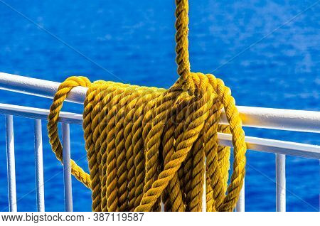Yellow Braided Rope Draped Over A Ship Railing