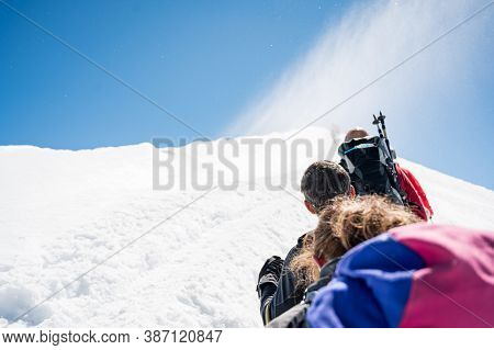 Rope Team Member Point Of View With Mountaineers Walking On Snow And Ice In Sunny Weather.