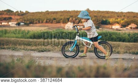 Caucasian Boy Riding The Bike In The Coutryside Wearing Hat In Sunny Summer Evening