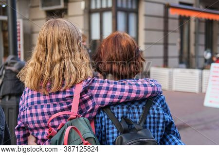 Back View Of Two Trendy Teen Girl Friends Hugging. Back View Portrait Of Two Affectionate Young Stud