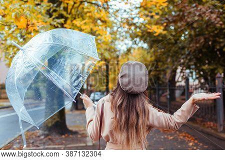 Woman Walking Along Autumn City Street Under Transparent Umbrella Checking If It Rains. Fall Season.