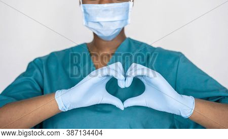 Female African Professional Medic Nurse Wear Face Mask, Gloves, Blue Green Uniform Showing Heart Han